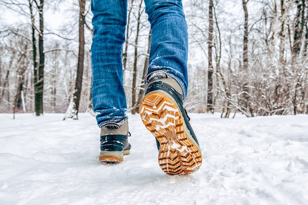 雪の中を歩くブーツで男の足 Premium写真
