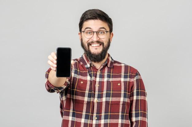 広告のためのスマートフォンを提示する魅力的な若い男の肖像 Premium写真