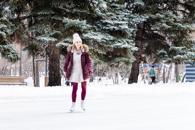 Красивая молодая женщина на коньках в снежном зимнем парке Premium Фотографии