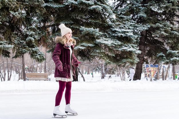 Девушка на коньках на замерзшем озере в снежном зимнем парке Premium Фотографии