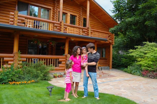 木造の家の近くの幸せな笑顔の家族 Premium写真