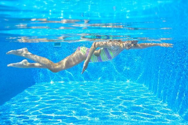 幸せなアクティブな子供がプールで水中を泳ぐ Premium写真