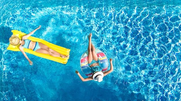 上からスイミングプールの子供たちの空中ドローンビュー、幸せな子供はインフレータブルリングドーナツとマットレスで泳ぐ、女の子はホリデーリゾートで家族での休暇中に水で楽しい Premium写真
