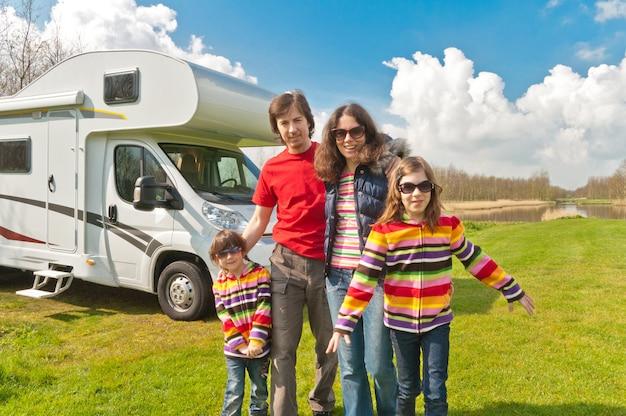 Семейный отдых, путешествие на автофургоне с детьми, счастливые родители с детьми в отпуске в автодоме Premium Фотографии
