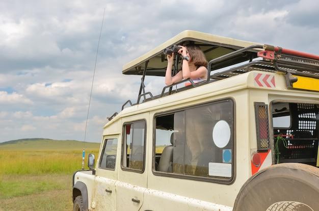アフリカのサファリで女性観光客、ケニアで旅行、双眼鏡でサバンナの野生生物を見て Premium写真