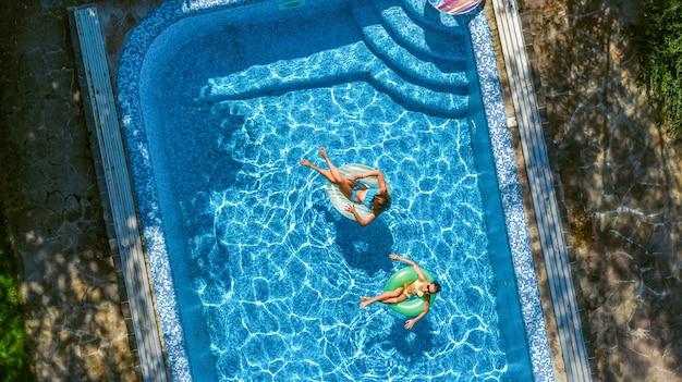 上からスイミングプールで子供たちの空中の平面図、幸せな子供はインフレータブルリングドーナツで泳ぐし、リゾートで家族での休暇中に水で楽しい時を過す Premium写真