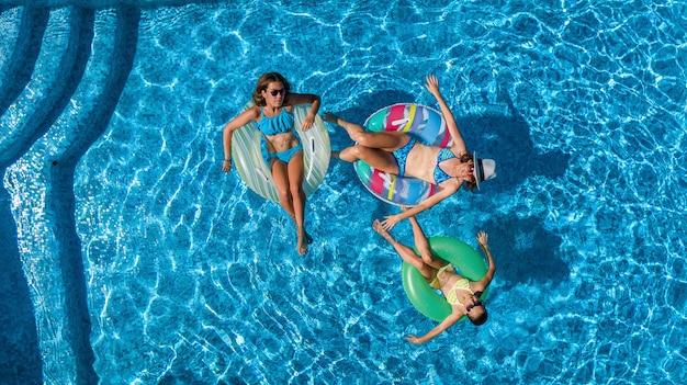 上からプールの空撮で家族、幸せな母と子供はインフレータブルリングドーナツで泳ぐし、家族での休暇、リゾートで熱帯の休日に水で楽しい Premium写真