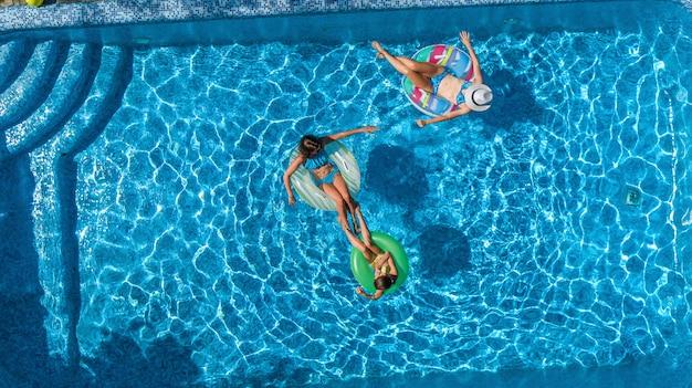 上からスイミングプール空中ドローンビューで家族、幸せな母と子供はインフレータブルリングドーナツで泳ぐし、家族での休暇、リゾートで熱帯の休日に水で楽しい Premium写真
