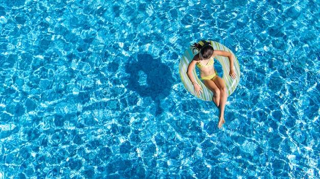 上からスイミングプールの女の子の空撮、子供は膨脹可能なリングドーナツで泳ぐし、家族での休暇に水で楽しい Premium写真