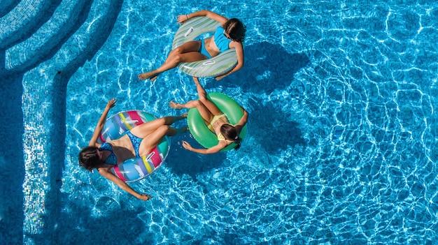 上からスイミングプールの空中ドローンビューで家族、幸せな母と子供はインフレータブルリングドーナツで泳ぐし、家族での休暇、リゾートで熱帯の休日に水で楽しい Premium写真