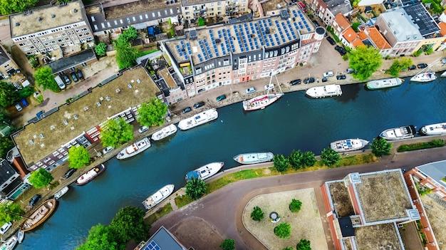 上から、運河と住宅、オランダ、オランダの典型的なオランダの街のスカイラインのデルフトの町の街並みの空中ドローンビュー Premium写真