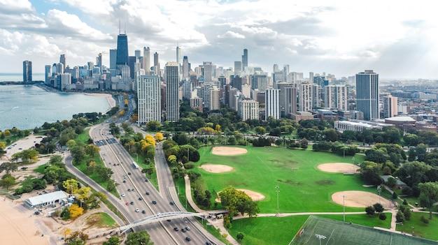 上からシカゴのスカイライン空中ドローンビュー、ミシガン湖、シカゴ市のダウンタウンの高層ビル都市の景観、公園、米国イリノイ州から Premium写真