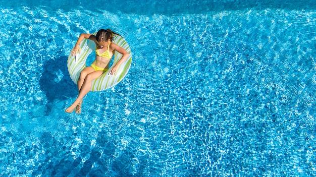 上からスイミングプールの空中上面で女の子を達成、子供はインフレータブルリングドーナツで泳ぐ、子供は家族での休暇のリゾートの青い水で楽しい Premium写真