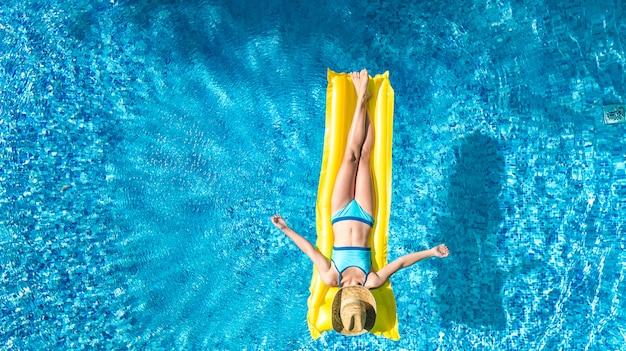 スイミングプールでリラックスした女の子、子供はインフレータブルマットレスで泳ぐし、家族での休暇、トロピカルホリデーリゾート、上から空中ドローンビューで水中で楽しい時を過す Premium写真