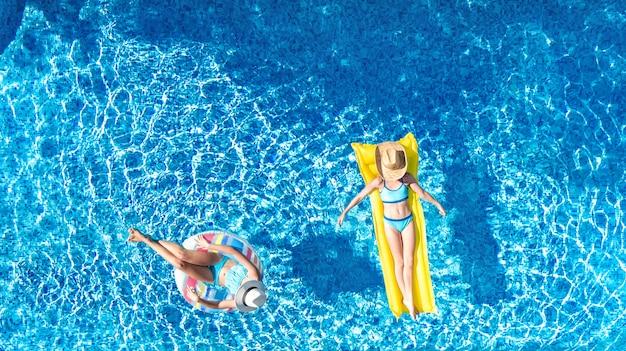 上記のスイミングプール空中ドローンビューの子供たち、幸せな子供たちはインフレータブルリングドーナツとマットレスで泳ぐ、アクティブな女の子はホリデーリゾートで家族での休暇中に水中で楽しい Premium写真