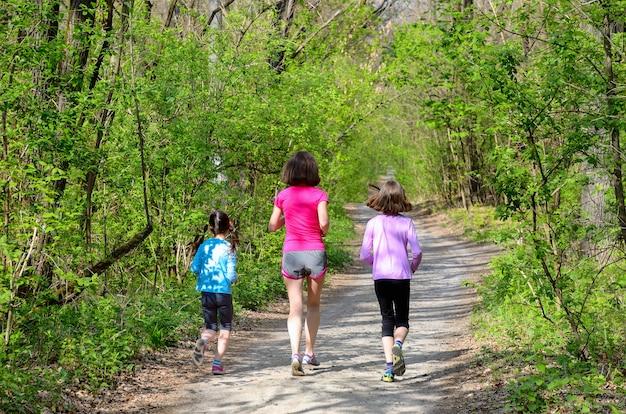家族のフィットネスとスポーツ、幸せなアクティブな母親と子供の屋外ジョギング、森で実行 Premium写真