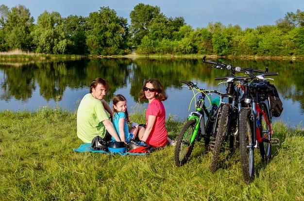 Семья на велосипедах на открытом воздухе, активные родители и ребенок на велосипеде и отдыха возле красивой реки, концепция фитнеса Premium Фотографии