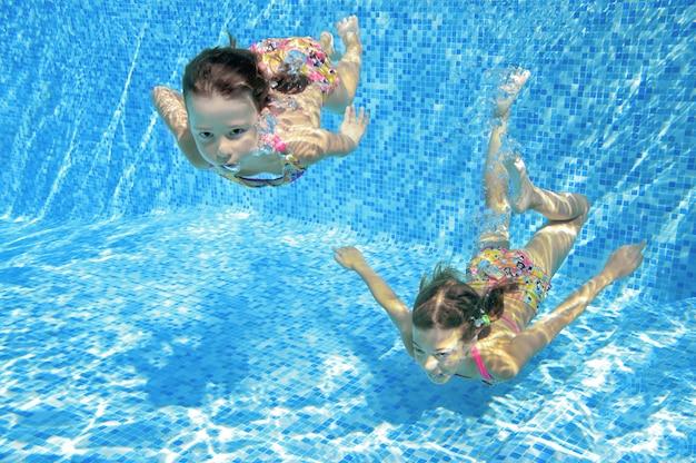 子供たちは水中プールで泳いで、幸せなアクティブな女の子はアクティブな家族の休暇で水、子供のフィットネス、スポーツを楽しんでいます Premium写真
