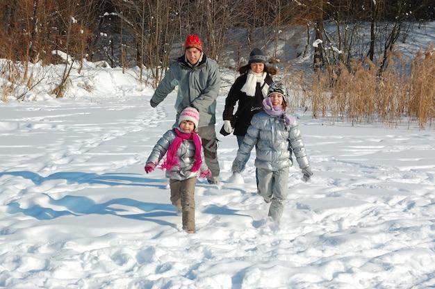 Счастливая семья гуляет зимой, веселится и играет со снегом на выходных в праздничные выходные Premium Фотографии