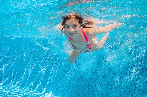 子供はプールで泳いで、幸せなアクティブな女の子がダイブし、家族での休暇に水、子供のフィットネス、スポーツを楽しんでいます Premium写真