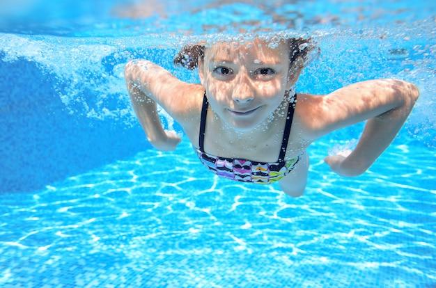 幸せなアクティブな水中の子供はプールで泳ぎます。水泳と家族の夏休みを楽しんで健康美少女 Premium写真