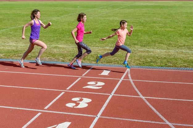 Семейный фитнес, мать и дети, бегущие по дорожке стадиона, тренировка и концепция спорта детей Premium Фотографии