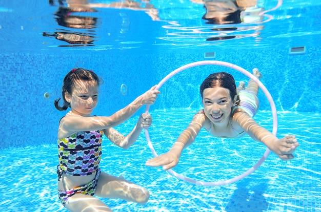 Дети плавают в бассейне под водой, счастливые активные девочки веселятся под водой, дети занимаются спортом на семейном отдыхе Premium Фотографии