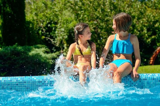夏のフィットネス、スイミングプールの子供たちは楽しさと水しぶき、家族での休暇に子供 Premium写真