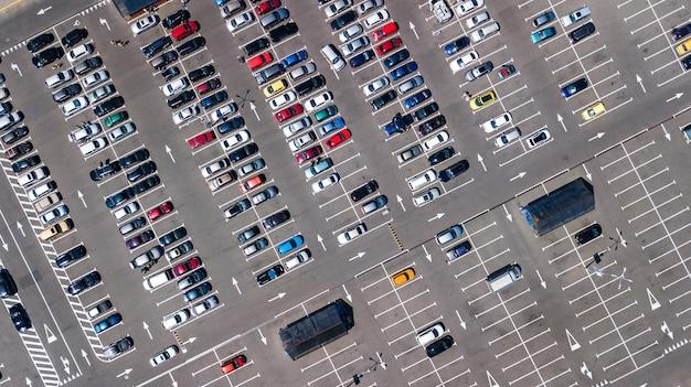 Воздушный беспилотный вид на стоянку с множеством автомобилей сверху, городской транспорт и городская концепция Premium Фотографии