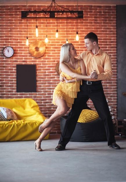 Молодая пара танцует латинскую музыку: бачата, меренге, сальса. две элегантные позы на кафе с кирпичными стенами Premium Фотографии
