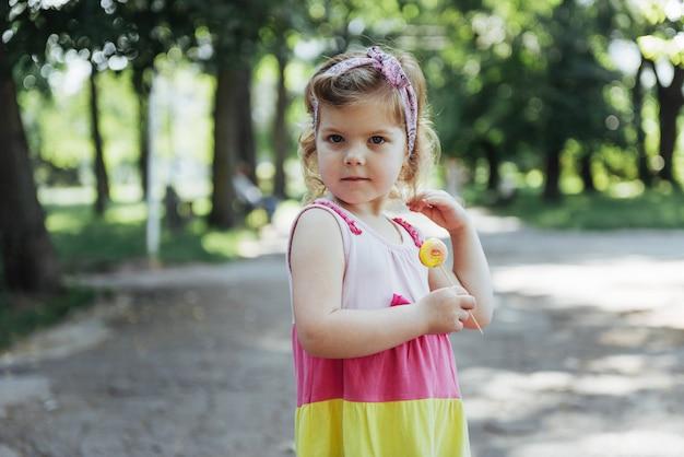Забавный ребенок с леденцом на палочке, счастливая маленькая девочка Premium Фотографии