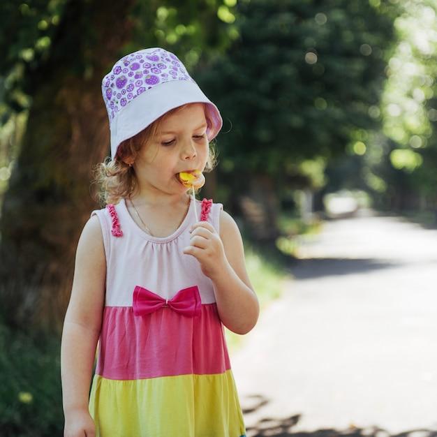 Забавный ребенок с леденцом на палочке, счастливая маленькая девочка ест большой Premium Фотографии