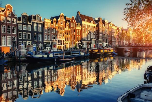 夕暮れの運河。アムステルダムは首都です Premium写真