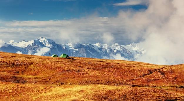 Палатка зелёная расстилается на перевале гуле. грузия, сванетия. Premium Фотографии