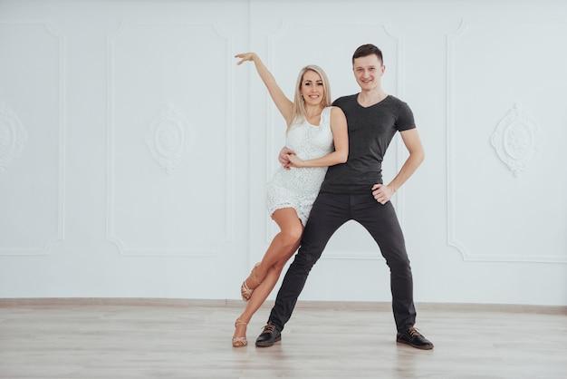 Молодая пара танцует латинскую музыку: бачата, меренге, сальса. две элегантные позы в белой комнате Premium Фотографии