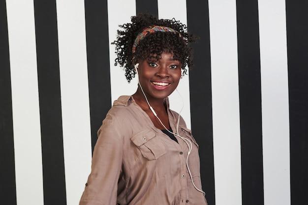 純粋な幸福。微笑んでいるアフロアメリカンガールは、背景に垂直の白と黒の線でスタジオに立っています。 無料写真
