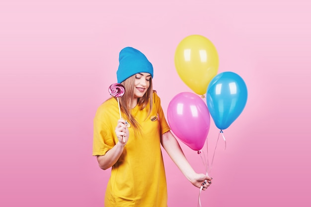 青い帽子の肖像画でかわいい面白い女の子は、空気のカラフルな風船とピンクに笑みを浮かべてロリポップを保持しています。幸せな笑みを浮かべて美しい多文化白人少女 Premium写真