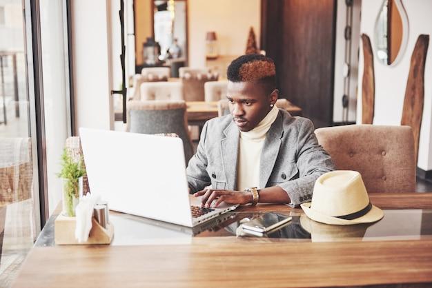 Афро-американский мужчина сидит в кафе и работает на ноутбуке Premium Фотографии
