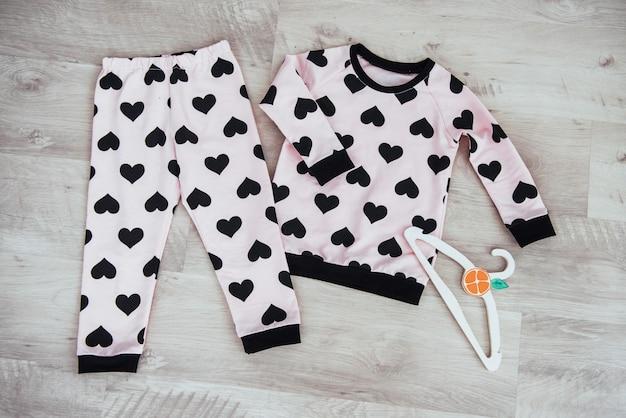 Набор детской одежды, изолированных на деревянном фоне Premium Фотографии