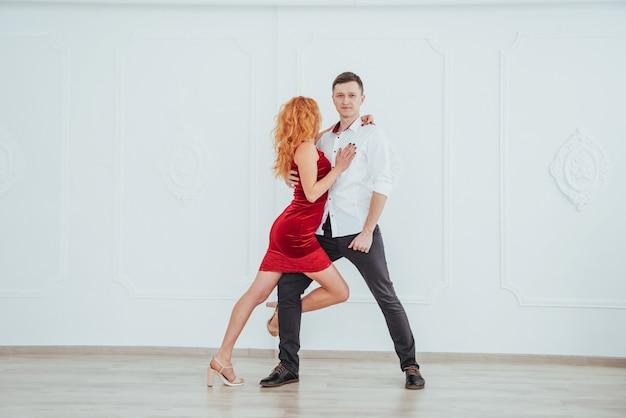 Молодая красивая женщина в красном платье и танцы человека изолированные на белой предпосылке. Premium Фотографии