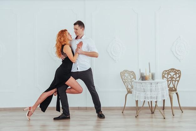 Молодая красивая женщина в черном платье и мужчина в белой рубашке танцы. Premium Фотографии