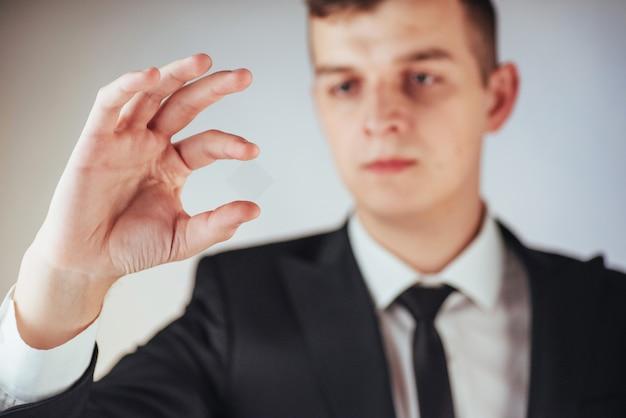 スーツの青年実業家は彼の手を示しています Premium写真
