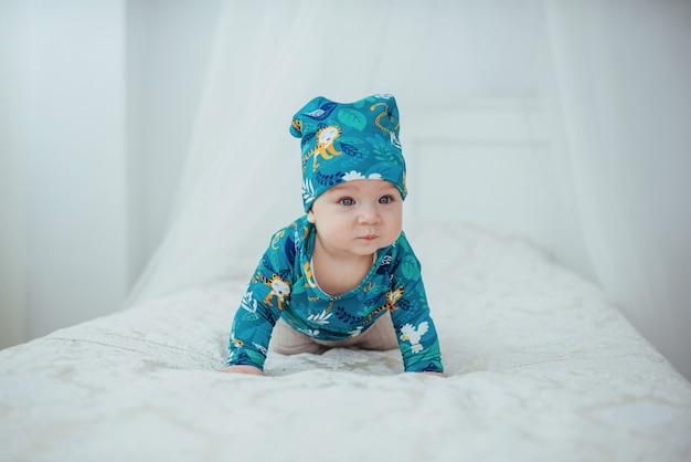 柔らかいベッドに横たわっている緑のスーツに身を包んだ新生児 Premium写真