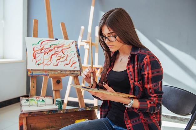 創造的な物思いにふける画家少女は、ワークショップでキャンバスにカラフルな絵をオイルの色でペイントします。 Premium写真