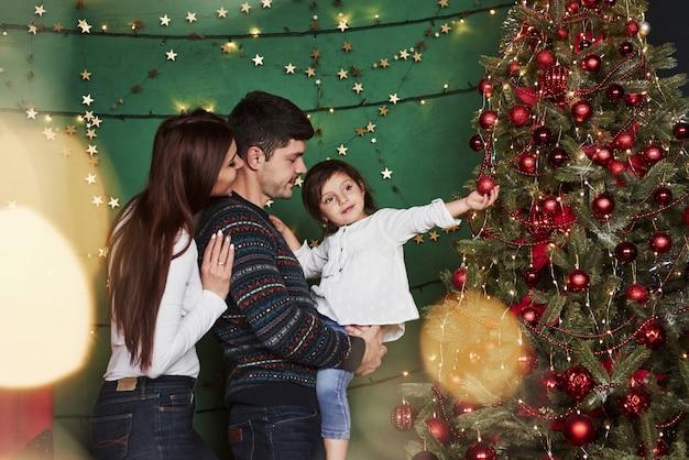 Милая маленькая девочка трогательно красный праздник сфера. счастливая семья празднует. новый год и стоя возле елки Premium Фотографии