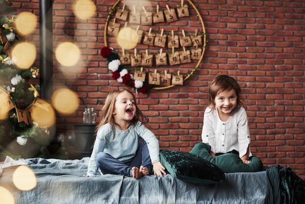 大笑い。バックグラウンドで休日のインテリアとベッドの上で楽しんで女の子 Premium写真