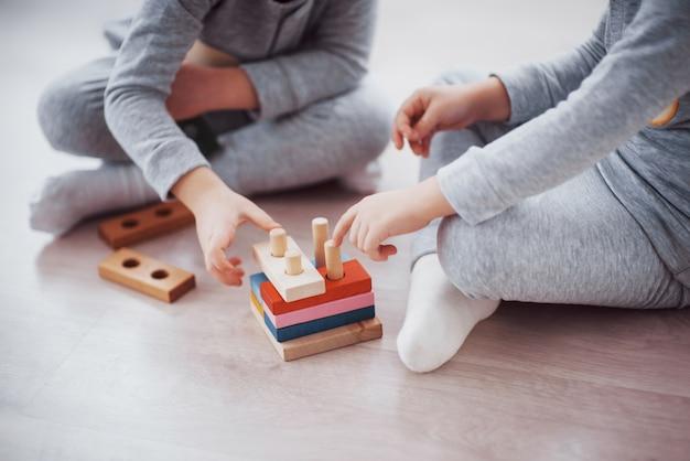 子供たちは子供部屋の床でおもちゃデザイナーと遊ぶ。 Premium写真