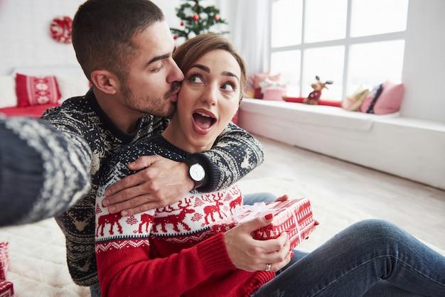 Женщина идет на своего парня, держа подарок. человек, принимая селфи его и его жены, одетых в новогоднюю одежду и сидя на полу в декоративной красивой комнате Premium Фотографии