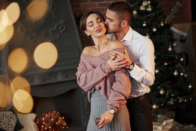 男は彼の最愛の少女にキスします。素敵なカップルは、クリスマスツリーの前でシャンパンと新年を祝うガラスを保持しています。 Premium写真