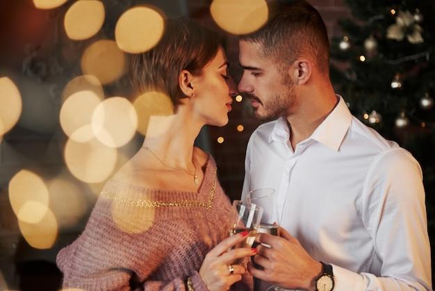 Почти поцелуй. хорошая пара празднует новый год в помещении с классической красивой одеждой на них Premium Фотографии